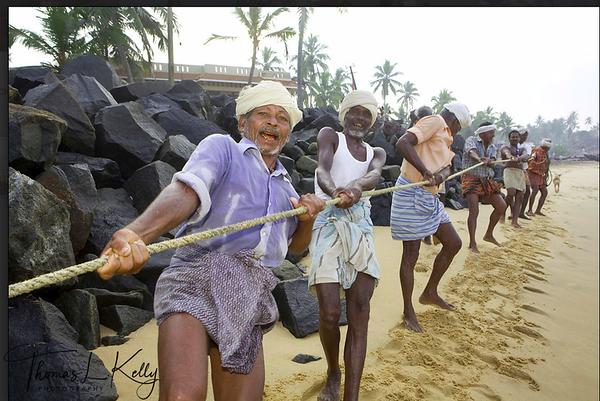 South Indian fishermen pull fishing net out on the shoreline of Kanya Kumari. India.