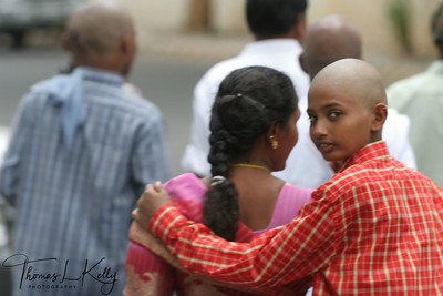 "Shaved headed boy with his mother . A head shaving in Balaji Temple is referred to as a ""hair-offering ceremony"". The purpose of this sometimes-disconcerting experience is to foster humility and purity, to mitigate past karma and for the good fortune."