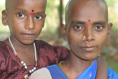 "Shaved headed mother and daughter. A head shaving in Balaji Temple is referred to as a ""hair-offering ceremony"". The purpose of this sometimes-disconcerting experience is to foster humility and purity, to mitigate past karma and for the good fortune."