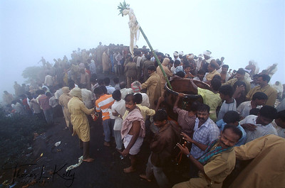 Within sight of the peak of Arunachala and oblivious to puring rain, devotees struggle to catch a glimpse of the holy vessel that will contain the sacred Krittika flame.