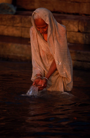An old Varanasi woman makes water offerings to Sun God, an early morning ritual, in Holy River Ganga of Varanasi, India.