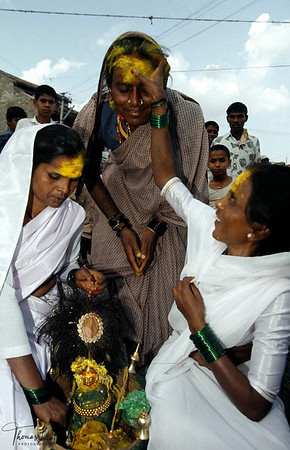Devdasi coloring one another's head with yellow vermilion powder. Saunadatti, India.