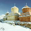 Snow covered Buddhist chortens mark the entrance to Karasha monastery, founded in the 11th century.  Zanskar, India.