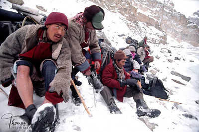 Porter slipped into the river filling their boot with freezing water. Wool socks are squeezed quickly of the water  preventing immediate frost bite. Zanskar, India