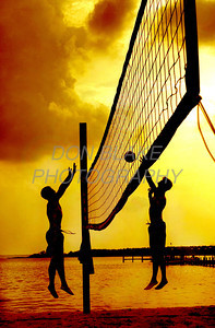 Friday, June 12, 2003, 5:56pm. A two on two volleyball game was played as the sun prepares to set on the bay side beach between The Rusty Rudder and The Lighthouse in Dewey Beach. photo/Don Blake