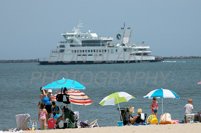 The Cape May-Lewes Ferry off the coast of the Delaware Bay as beach goers enjoy the sun on Lewes Beach. The Dialog/Don Blake