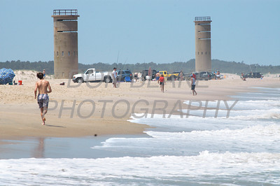 Beach goers enjoy the surf and sun on beach at Cape Henlopen State Park with the World War II Observation Tower in the background. The Dialog/Don Blake