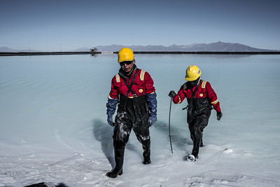 Two workers from the lithium plant leaving one of the evaporation pools after taking some samples of brine for the concentration tests. In the salt brines of this salt desert is more than 50% of the world's lithium, whose demand will increase with the manufacture of the following generations of electric vehicles. May 12 of 2015, Llipi, Potosi, Bolivia.