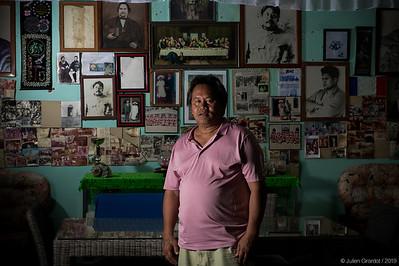 """Jacky CHUNG in front of a wall of pictures, in the Teuruarii royale's family home. On the left top corner, a picture of Tiki A'a, symbole of the old gods, is standing next to the """"said to be monarch Teuruarii"""", symbol of the protestant religion.  // Jacky CHUNG devant un mur de photographies et d'illustrations anciennes, dans la maison de la famille royale Teuruarii. Tiki A'a, symbole des anciens dieux, se tient à côté du """"dit monarque Teuruarii"""", symbole de la religion protestante."""