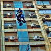 """A window cleaner above the sidewalk across the street, cleaning windows """"with flare"""" showing off to his audience below. Spotted in Buenos Aires, Argentina."""
