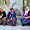 Three women sittin on the sidewalk. Spotted in Konya, Turkey.