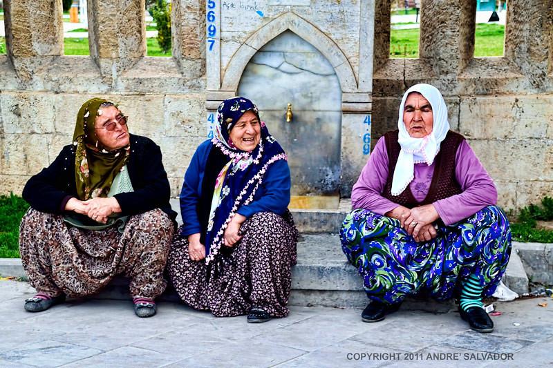 Three women sittin on the sidewalk. Spotted in Konya, Turkey.