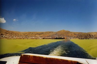 Lake Titicaca grows algae on top because of the nightly cold temperatures at the high altitude contrasting with the direct sunlight during the daytime. As a boat drives through the water you see that the algae separates as the boat cuts through....Note how the algae ripples atop the water's surface.