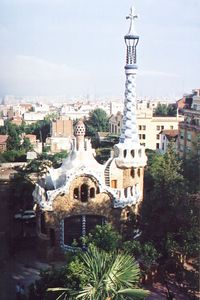 Gaudi  - Park Guell .............   Two pavilions at the main entrance complete the wall surrounding the park. Intended as a porter's lodge and administrative building, these pavilions are of stone with roofs of Catalan vaults of flat-laid brick finished with pieces of broken ceramic called trencadís. The ceramic trencadís follows the sinuous geometric surfaces, a device which gives all of the park's ornamentation a unique beauty. Each of the roofs is crowned by a small dome and above all stands a tall, spiral-shaped tower adorned with colorful tile and topped with Gaudí's characteristic four-branched cross.