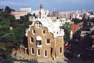 """""""Gaudi"""" - Park Guell ...............................................  Two pavilions at the main entrance complete the wall surrounding the park. Intended as a porter's lodge and administrative building, these pavilions are of stone with roofs of Catalan vaults of flat-laid brick finished with pieces of broken ceramic called trencadís. The ceramic trencadís follows the sinuous geometric surfaces, a device which gives all of the park's ornamentation a unique beauty. Each of the roofs is crowned by a small dome and above all stands a tall, spiral-shaped tower adorned with colorful tile and topped with Gaudí's characteristic four-branched cross."""
