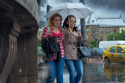 Happy Rainy Day | Street Photography in Bucharest Romania at Piata Universitatea Two Girls with Umbrella and Taxi in the Rain at University Square Photo
