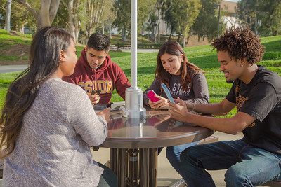 Students and seniors sitting at the Senior gift which is a solar powered charging umbrella and table.