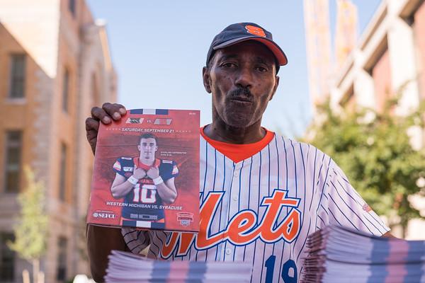 Program seller Joseph Godly sells game guide before the start of the game.