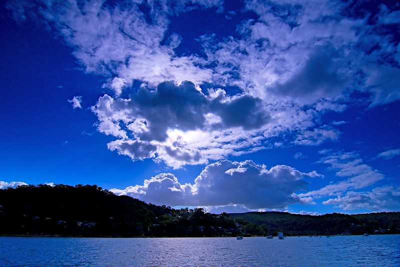 Bright sky art image. White Cumulus cloud in mid blue sky. Australia.