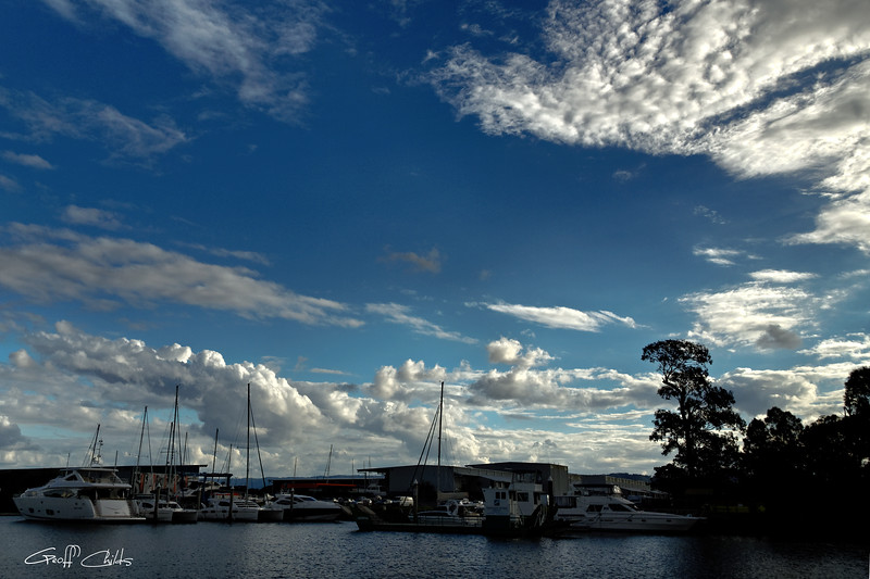 White Cumulus cloud in a blue sky over a marina with watercraft.