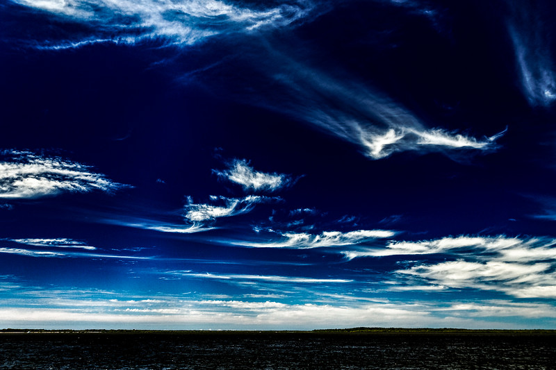 Vivid white Cirrus cloud in dark blue sky.