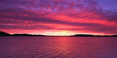 Magenta coloured altostratus cloudy Sunrise Seascape Panorama.