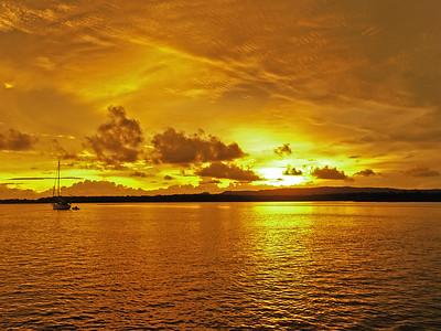 Golden coastal cloudy sunrise seascape.