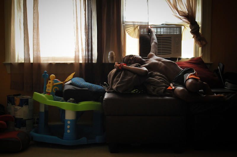 Caressa's son relaxes in front of the air conditioner on a hot summer day.