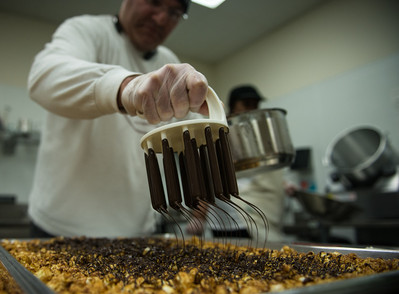 Rich Arslan, owner of gourmet popcorn's Popped Republic, drizzles the Dark Chocolate-Drizzled Capitol Caramel.