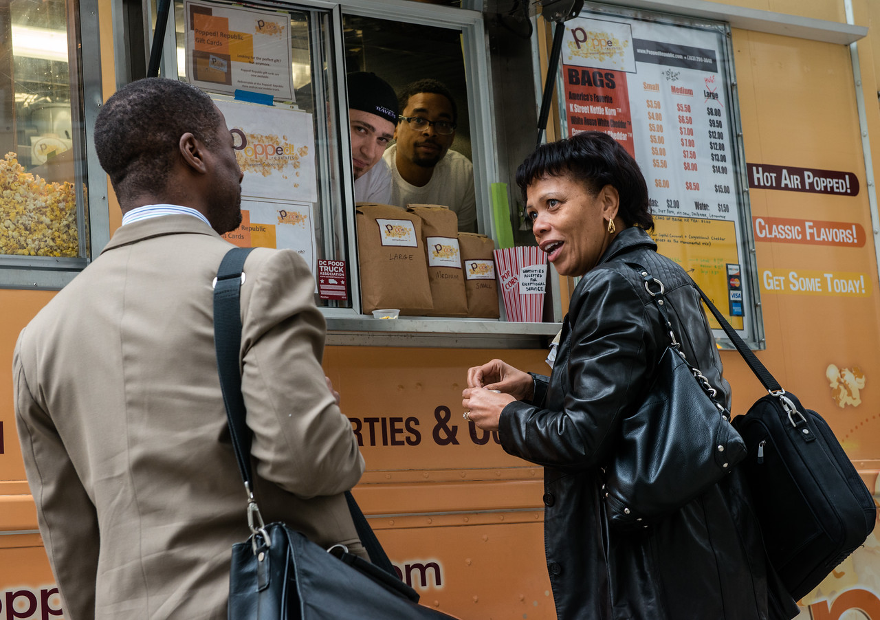 Donna Wilson and Ramien Pierre sample some of the many different popcorn flavors offered by the Popped Republic food truck in DC.
