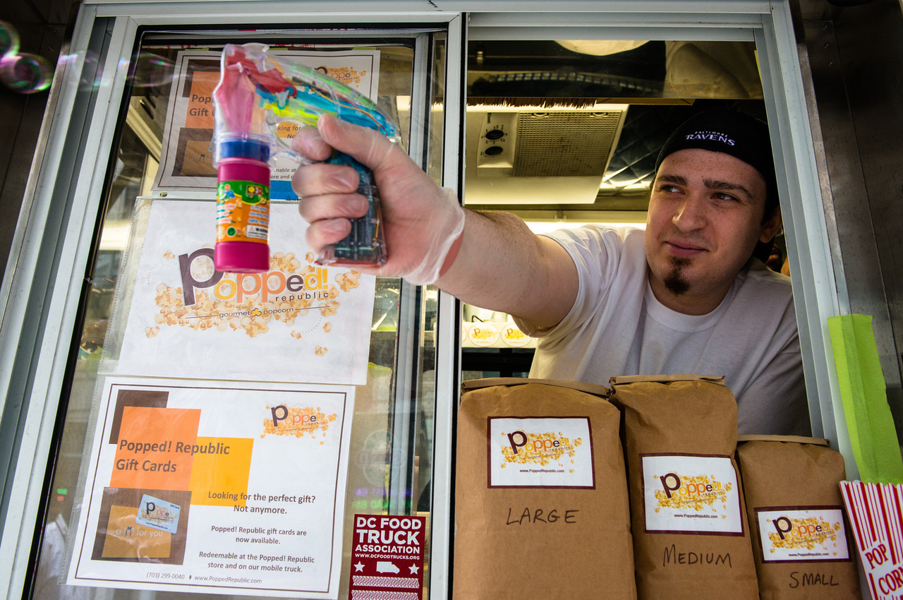 Morie Newman of Popped Republic uses a bubble gun to lure customers to the food truck.He says bubbles go pop, too.