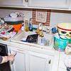 White kitchen sink, tile counters, tile backsplash, dining room and kitchen have tile floor