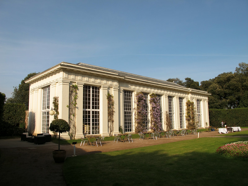 The elegant Orangery at Edgcumbe House, full of guests at a wedding reception.