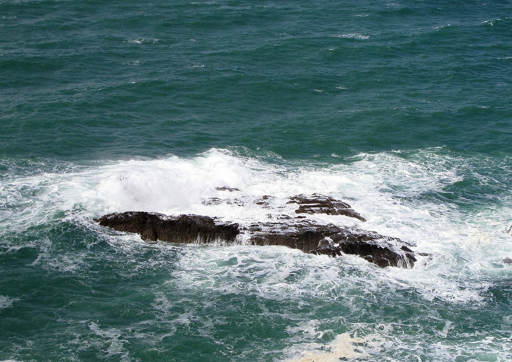 A gentle swell crashes over semi submerged rocks in Lannacombe Bay.