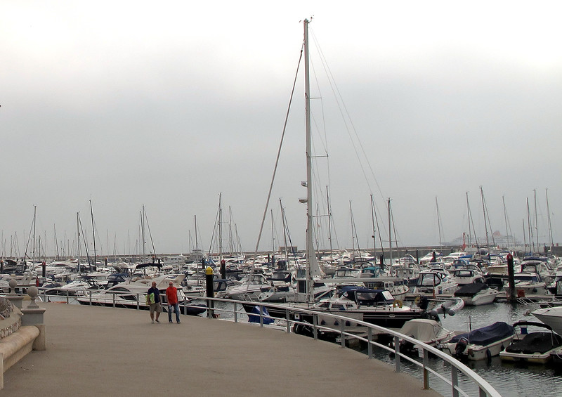 The marina at Torquay with a cruise ship lurking in the mist offshore.