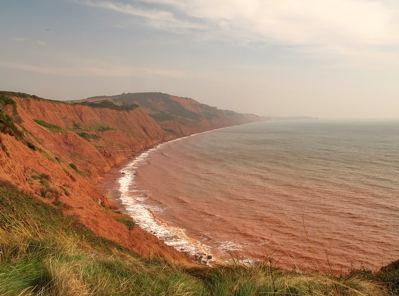 The sea is turned red from the mud of these eroded cliffs.