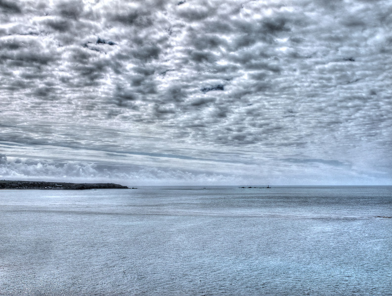 Clouds loom over Land's End, The Longships Rocks and lighthouse.