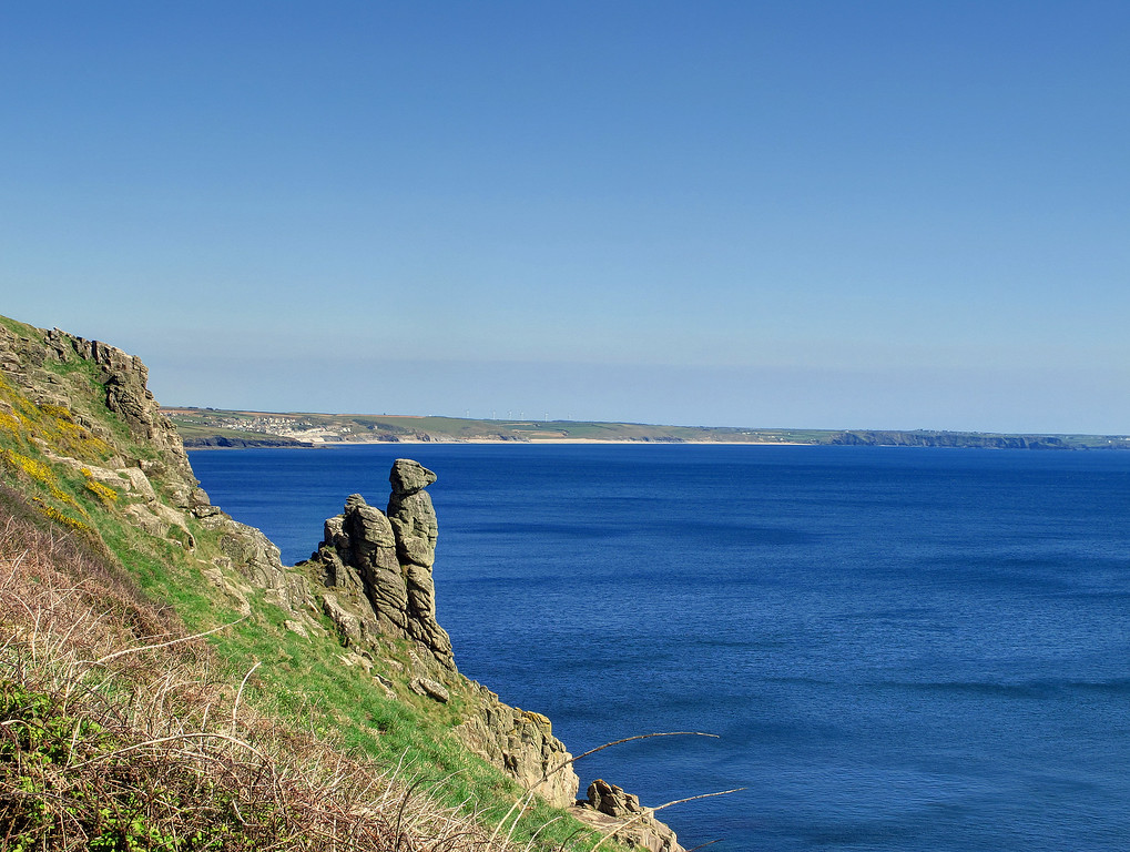 An outcrop of rock which is very reminiscent of a Meercat gazing out to sea.    The destination Porthleven can be seen on the other side of the bay.