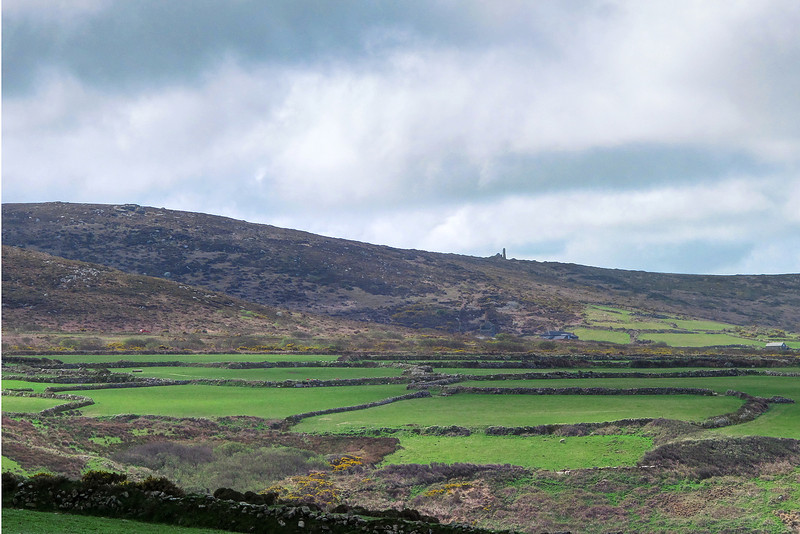 The small fields contained in stone walls in the foreground are thought to have originated in the Bronze Age, whereas the old engine house on top of the hill at Bosigran Farm is quite recent, dating from the 18-19th century.