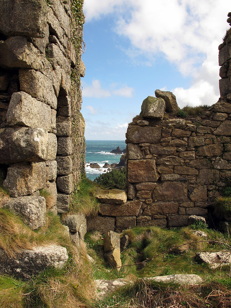 An abandoned and ruined mining building near Lean Point, its rocks visible through the hole in the wall.