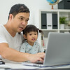 Man holding the kid  at the laptop, dad hugs a daughter, Asian family using the computer, Happy kid is smiling, Teaches his daughter to work with laptop. father and daughter looking at laptop at home