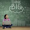 Cute schoolgirl looking at word of think big