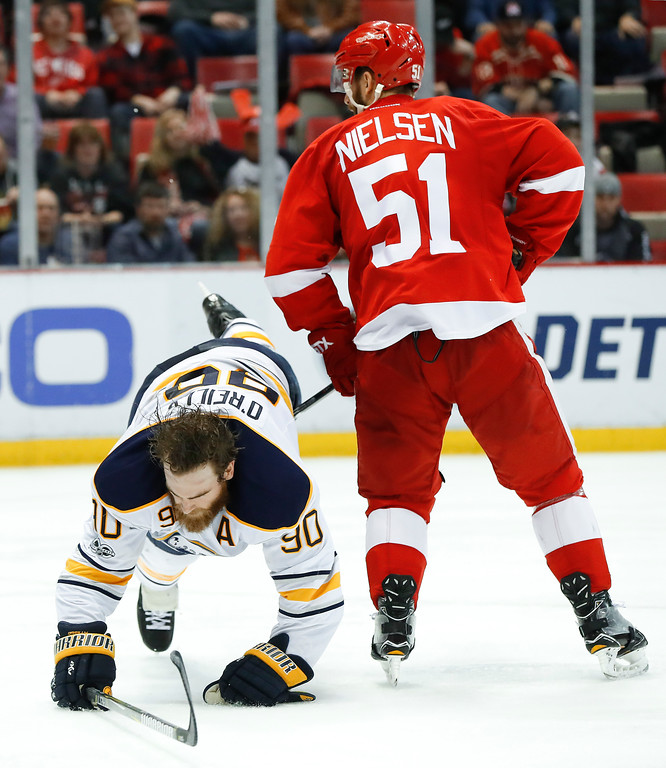. Detroit Red Wings center Frans Nielsen (51) dumps Buffalo Sabres center Ryan O\'Reilly (90) in the third period of an NHL hockey game Monday, March 20, 2017, in Detroit. (AP Photo/Paul Sancya)