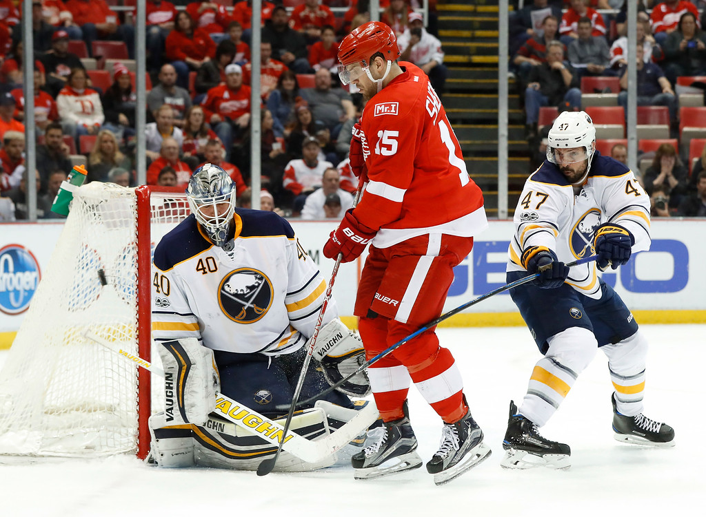 . Detroit Red Wings center Riley Sheahan (15) tries to deflect a shot at Buffalo Sabres goalie Robin Lehner (40) in the second period of an NHL hockey game Monday, March 20, 2017, in Detroit. (AP Photo/Paul Sancya)