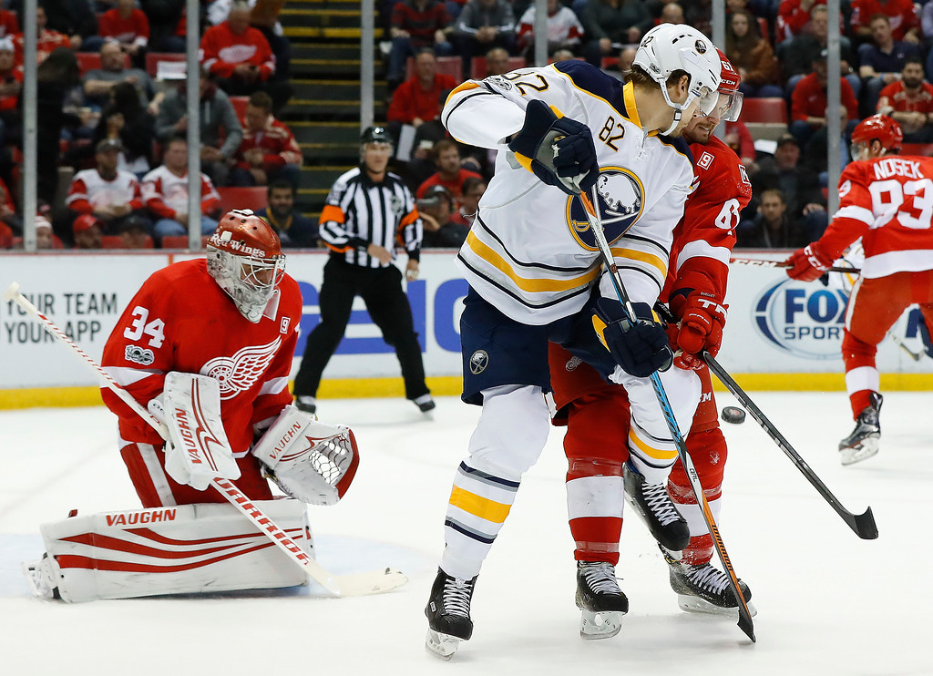 . Detroit Red Wings\' Xavier Ouellet, right, defends Buffalo Sabres Marcus Foligno as a shot is deflected towards goalie Petr Mrazek in the first period of an NHL hockey game Monday, March 20, 2017, in Detroit. (AP Photo/Paul Sancya)