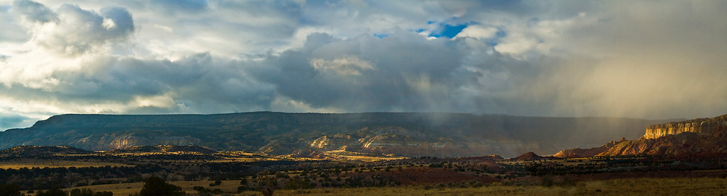 Desert Joy<br /> By Claudia Tammen<br /> <br /> Comments:<br /> I took this at Ghost Ranch, NM, on a trip in late Nov. 3 photos are stitched to create a panorama. A late afternoon squall is dispersing and I was hoping for a rainbow. However, this image shows the striking afternoon light and lively skies of the NM desert landscape.