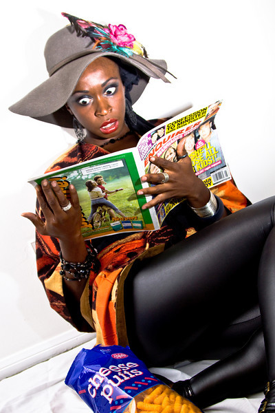 Reading the Tabloids<br /> By Vivian Frerichs<br /> <br /> Note:<br /> My friend, Chioma Nwosu, is a member of the Screen Actors Guild and an accomplished actress. She agreed to model for me for this shot, using some of her more flamboyant, and I think very appropriate, wardrobe for this photo.<br /> Shot using strobes mixed with window light.