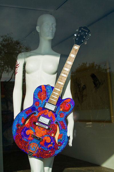 Nude with Guitar<br /> By Claudia Tammen<br /> <br /> Note: Nude with guitar was taken at Laguna Beach. She captured my attention standing in an art gallery window. I liked the contrast between the stark white nude mannequin and the very colorful guitar. She is quite regal and very unlikely!