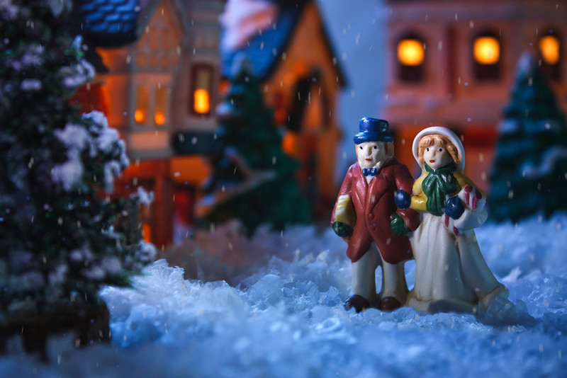 Miniature Chill<br /> By John Gasca<br /> <br /> This is a ceramic Christmas village. The houses have bulbs inside and<br /> plug in to light them up. The people are about 2 inches tall. The<br /> scene was backlit by hanging a white sheet from two light stands and<br /> firing a strobe through the sheet at 1/8 power. The strobe was gelled<br /> with 3/4 CTB (Blue Gel)  to give it a chilly winter evening look and<br /> provide the background between the houses. Two LED pen lights were<br /> used to side light the people and top light the foreground pine tree.<br /> Snowfall was created digitally in 3D Max and added in Photoshop. View<br /> the largest (Original) image size to see more detail.