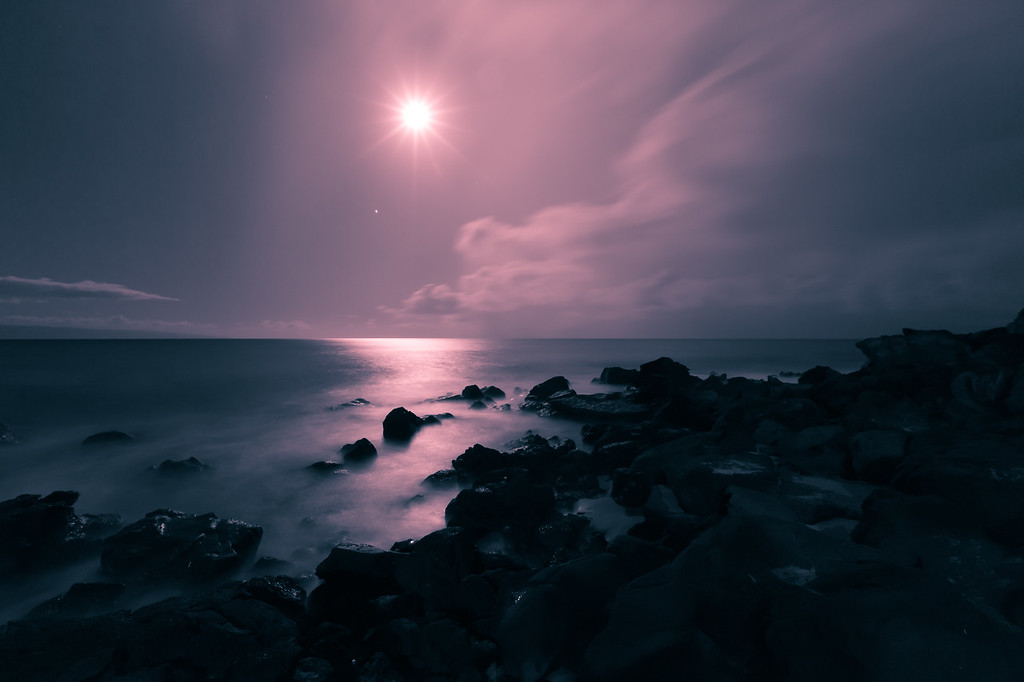 "<h2>Earth's Rhythm</h2> </br><p>The moon is heading toward setting with Venus leading the way to the horizon.  The view is from Maui looking East.  The island creeping in on the left is Lanai.  I woke at 4:30AM and went out on the balcony and saw what a beautiful night is was so I went for a short walk with my camera.  After capturing this image I was chased in by the rain.</p></br> <p>I setup the camera so that I could have a long exposure for the soft fluffy waves and a small aperture so the moon would have a star affect.  The wide angle lens was used to get a nice expanse of the shore and to minimize the star/planet streaks.</p></br> <p>In Lightroom I converted this to a duo-tone of red and blue. (You can see the original <a href=""http://www.clightpictures.com/Travel/Hawaii-2011/i-sGzfLN7/2/X3/MG9986-X3.jpg"">here</a>)</p>"